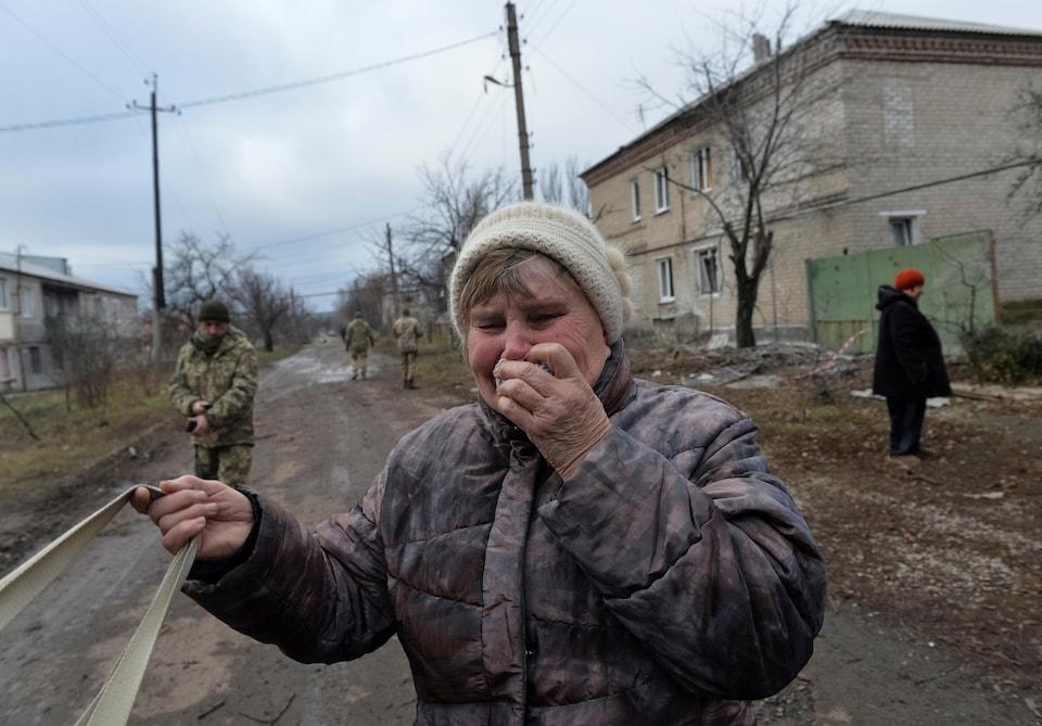 Une femme pleure dans une rue boueuse. Des soldats se trouvent derrière elle.