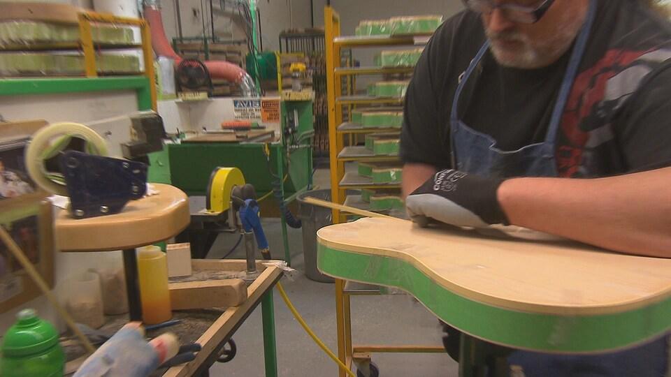 Un homme fabrique une guitare Godin dans l'usine de Richmond.