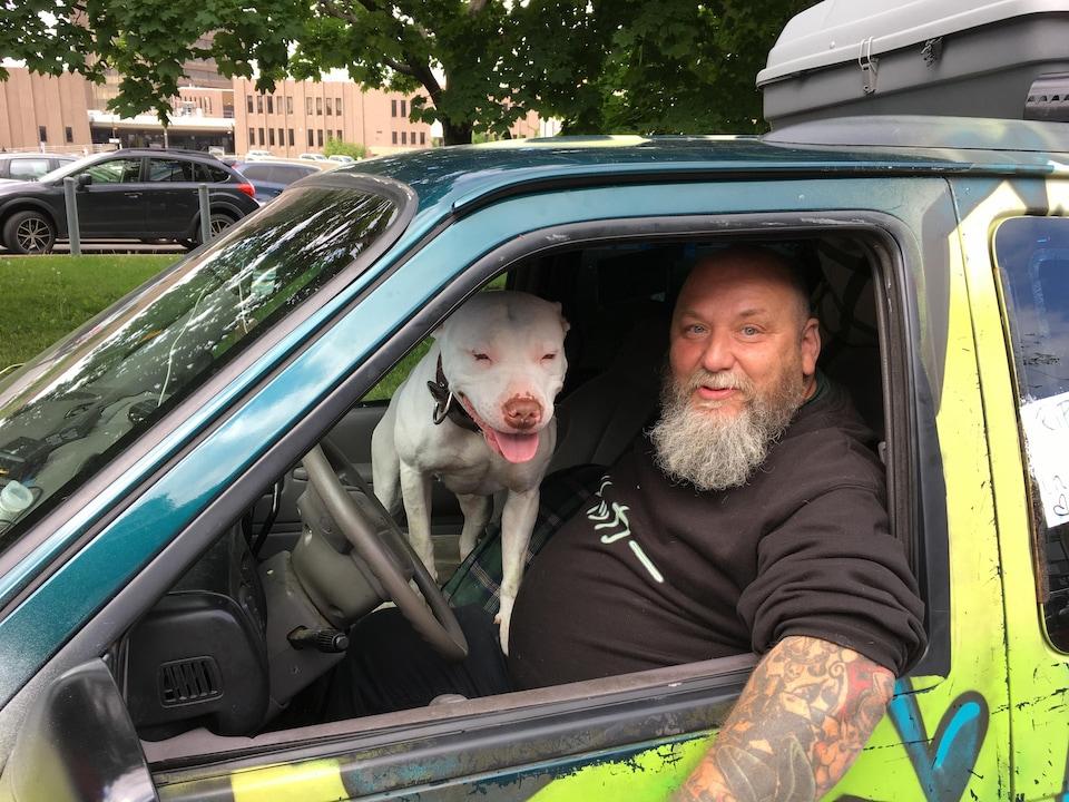 Guylain, la barbe blanche et des tatous sur les bras, assis dans sa fourgonnette avec son gros chien blanc.