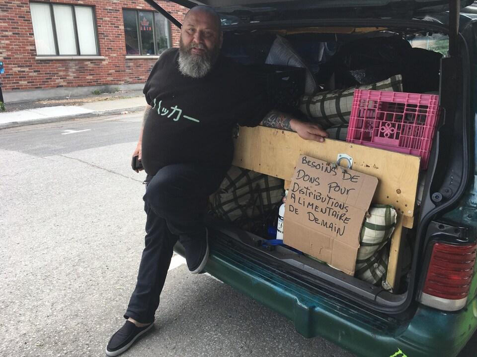 Guylain est appuyé sur son camion. Sur une pancarte en carton, on peut lire : «Besoins de dons pour distribution alimentaire de demain».