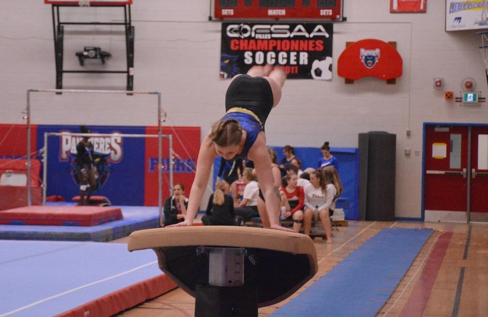Une gymnaste qui fait une voltige sur un appareil.