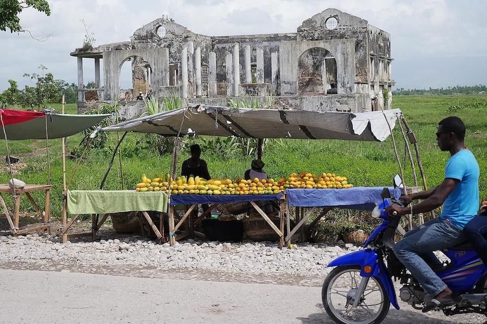 Des vendeurs de mangues à Haïti, en face d'un immeuble détruit par le séisme de 2010 et un homme en moto à l'avant de cette scène.