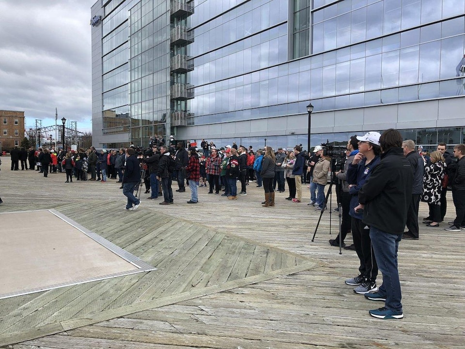 Une centaine de personnes regardent vers la mer