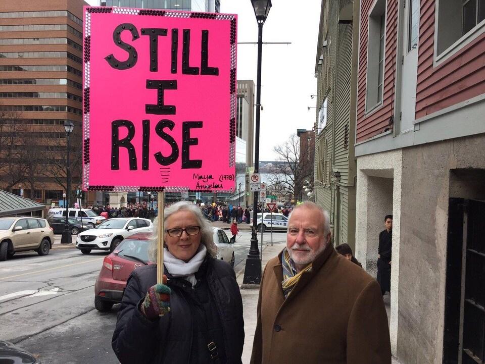 Une femme et un homme manifestent avec une pancarte