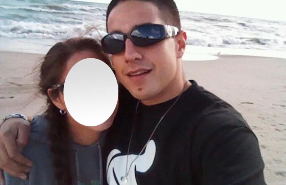 Photo d'un homme qui tient une femme par l'épaule sur la plage.