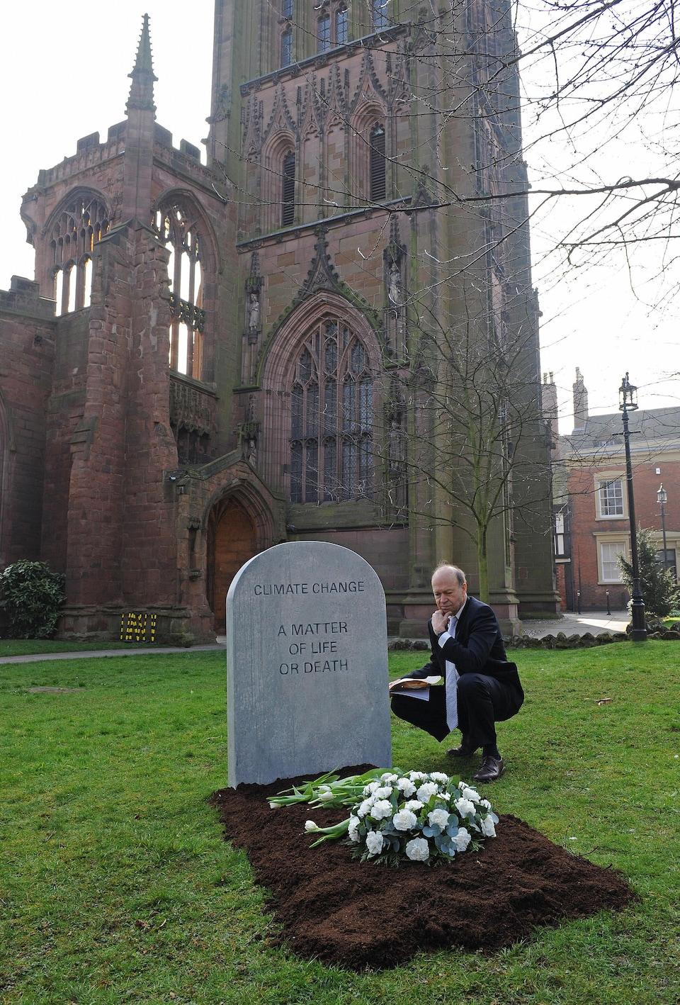 James Hansen est accroupi à côté d'une fausse pierre tombale sur laquelle il est écrit «Changement climatique : une question de vie ou de mort» en anglais.