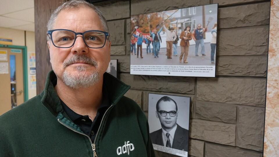 Harold Robert devant le mur commémoratif de l'école de la résistance.