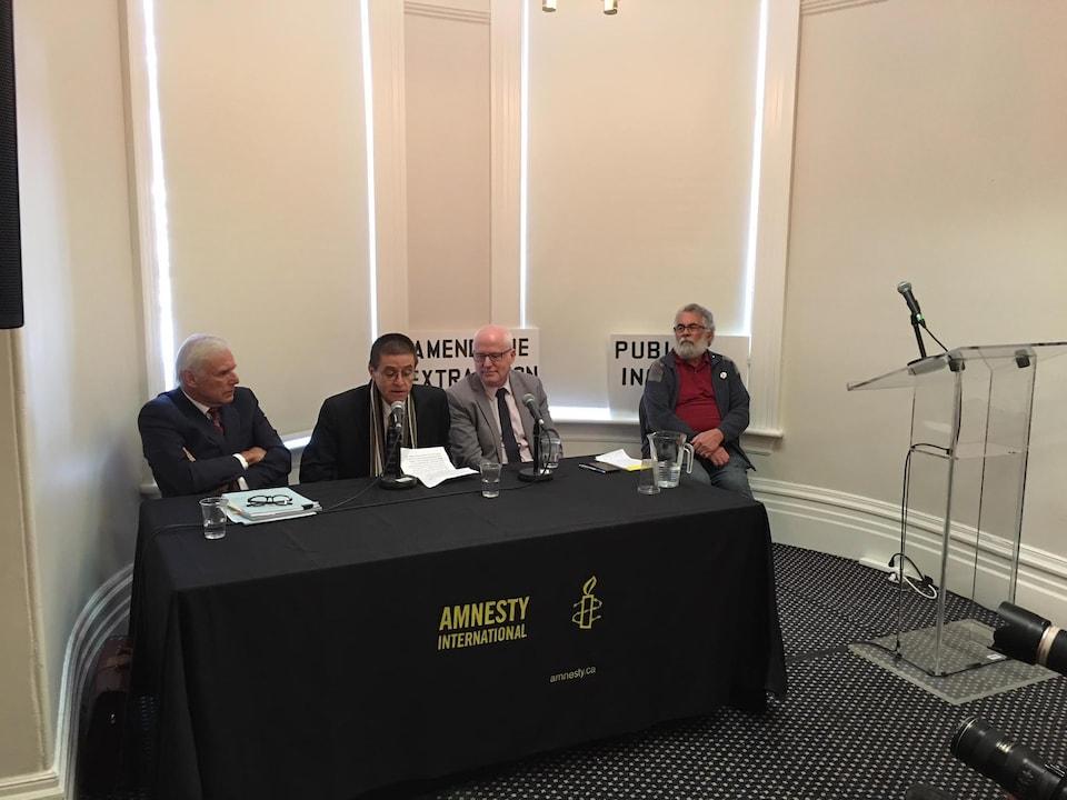 L'homme est entouré de son avocat et du secrétaire d'Amnistie internationale.