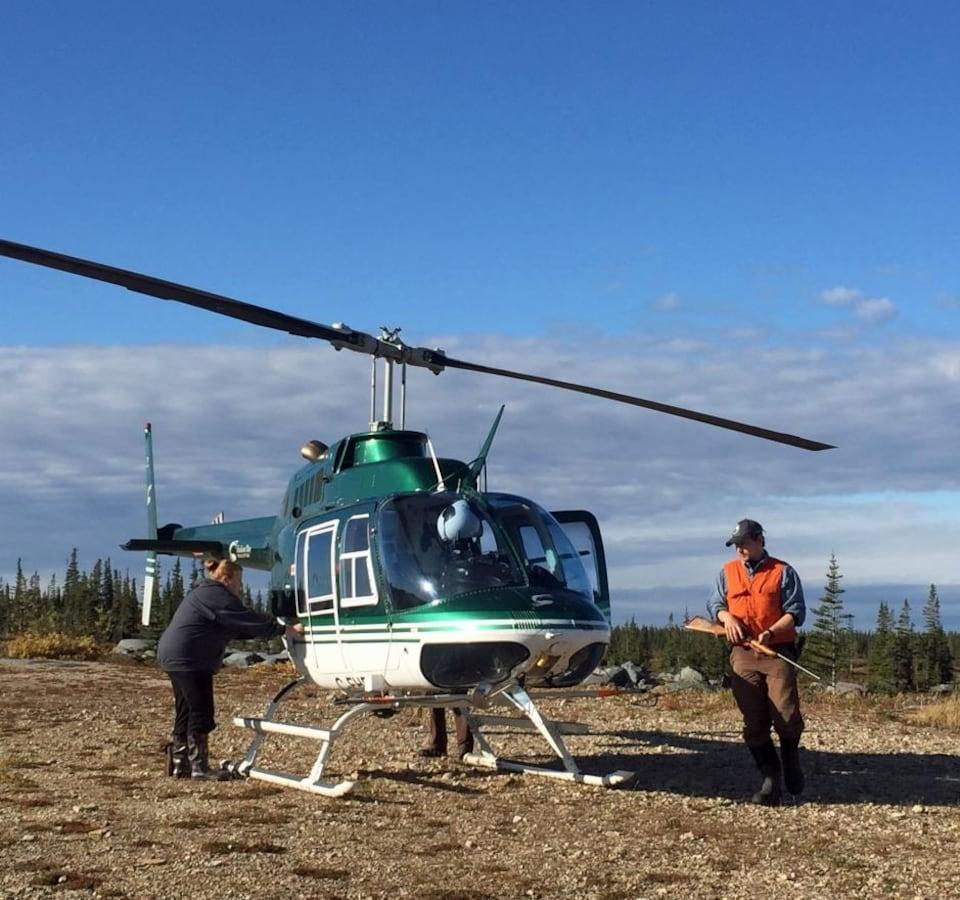 Des scientifiques équipés de fusils tranquilisant s'apprêtent à monter à bord d'un hélicoptère.
