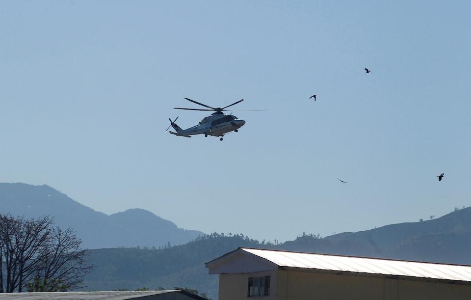 Un helicoptère vole dans le ciel pakistanais, sur fond de montagne. Des oiseaux volent à sa droite.