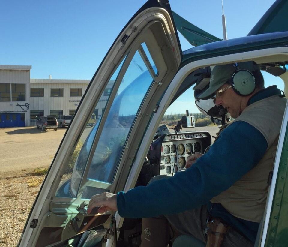 Un pilote s'apprête à fermer la porte d'un hélicoptère.