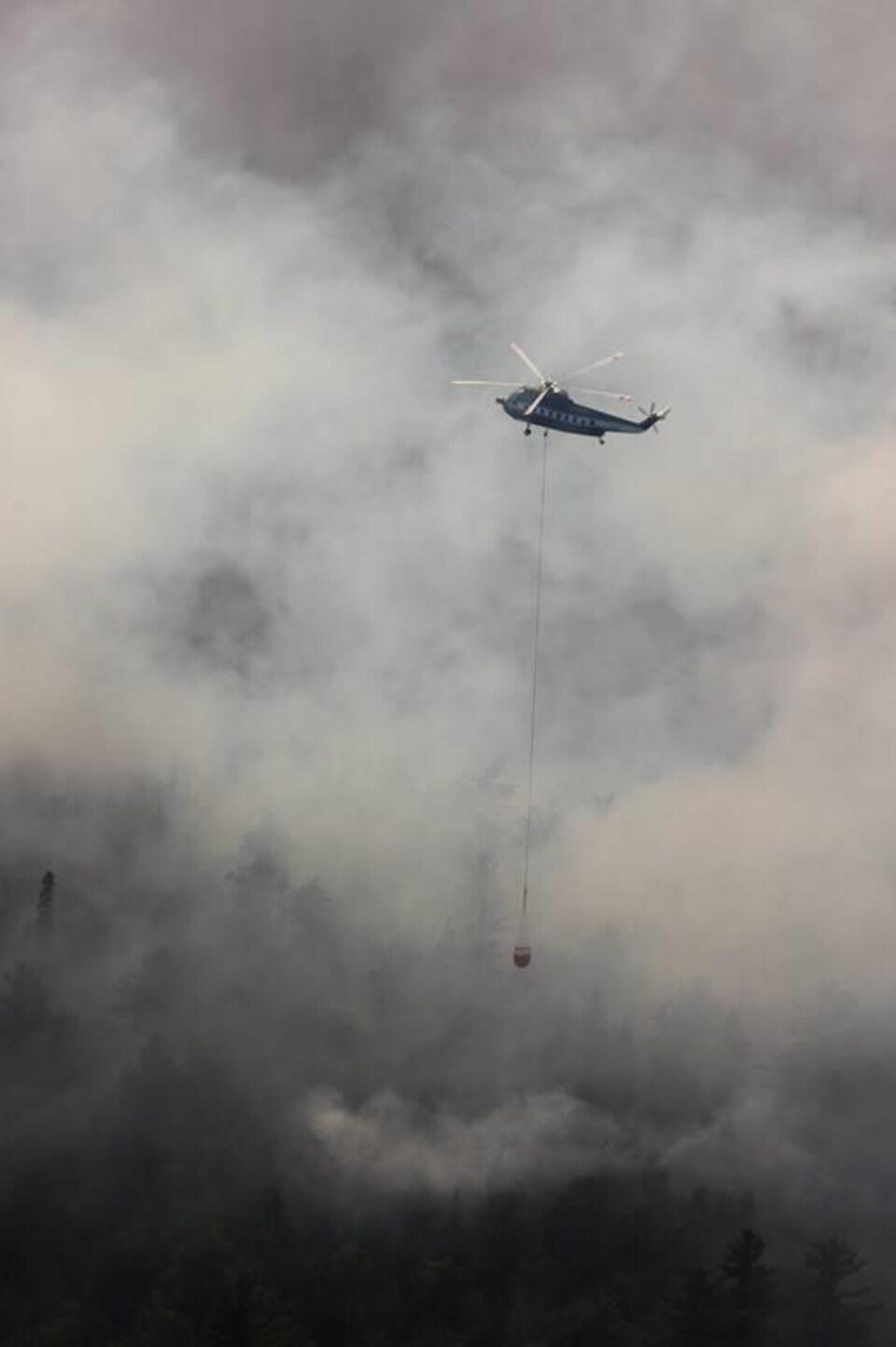 Hélicoptère en plein vol dans un ciel enfumé.