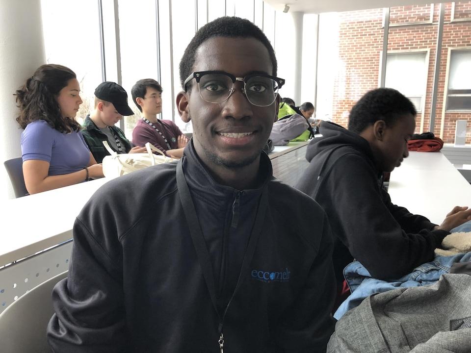 un jeune homme qui porte des lunettes et une veste noire