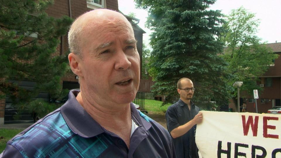 Geroge Brown répond aux questions des journalistes. Derrière, un homme tient un affiche avec le message «We are Heron Gate» (Nous sommes Heron Gate).