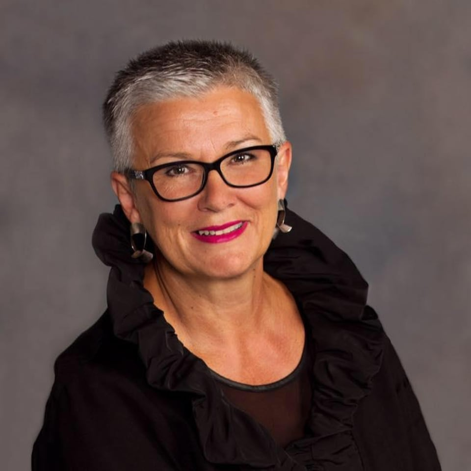 Portrait d'une femme souriante. Elle porte des lunettes et des boucles d'oreilles