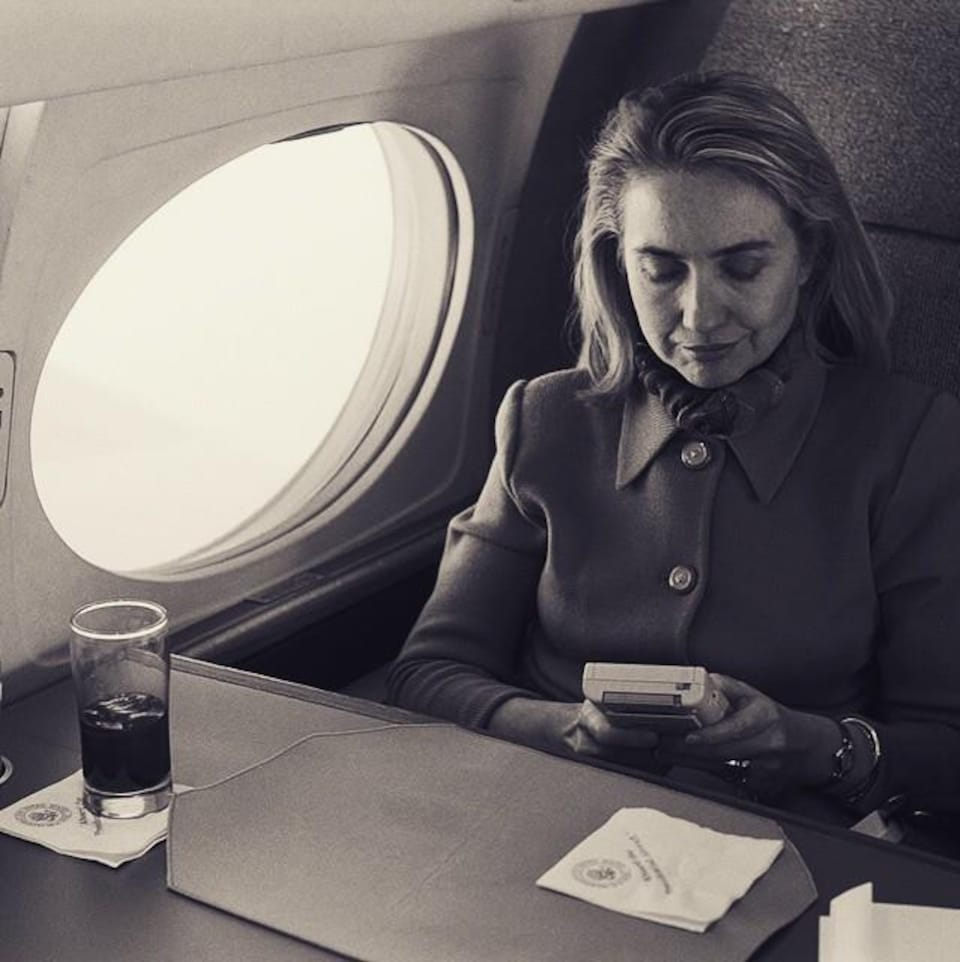 Une photo en noir et blanc d'Hillary Clinton assise dans un avion en train de jouer au Game Boy.