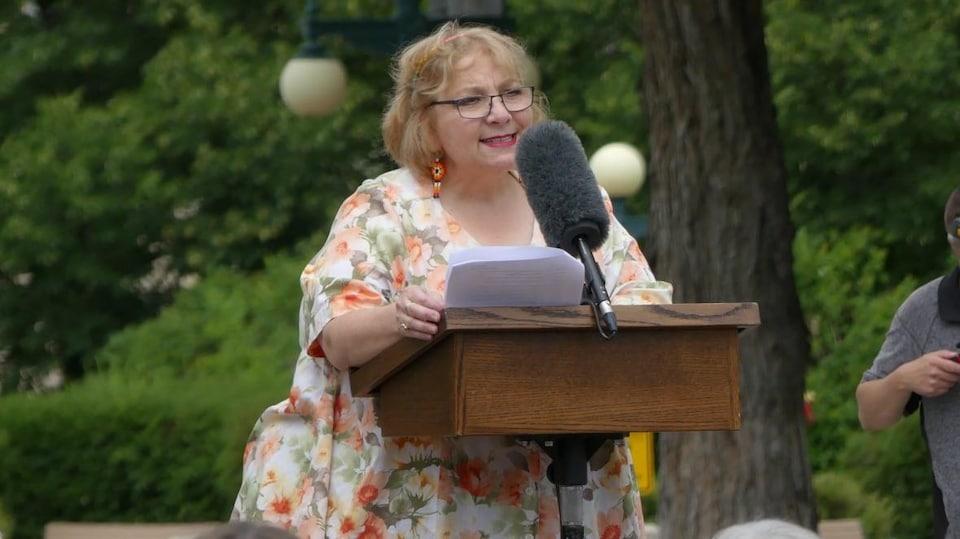 Paulette Duguay debout qui parle dans un micro.