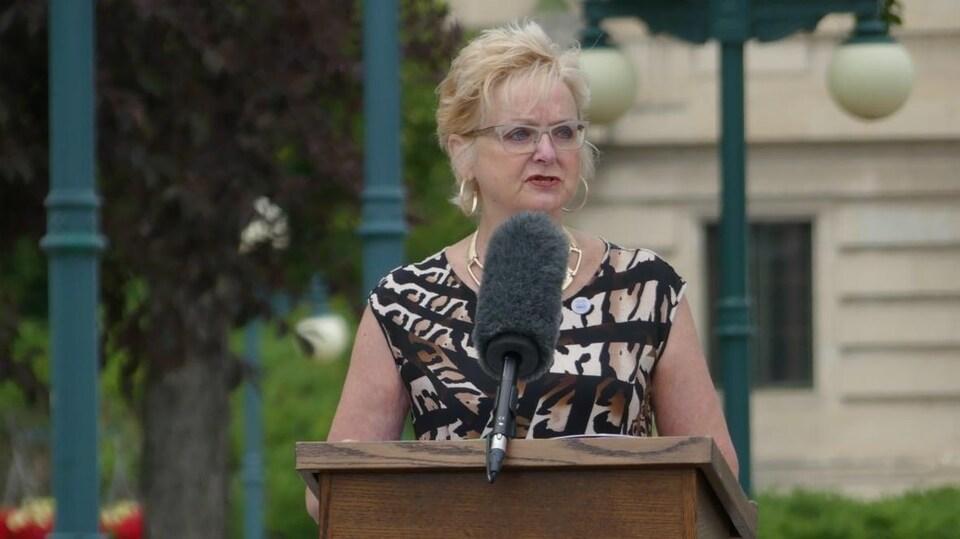 Myrna Driedger debout qui parle dans un micro.