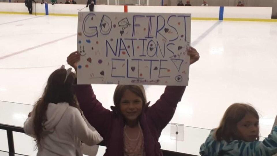 Dans les gradins d'un aréna, une jeune fille porte une pancarte sur laquelle est inscrit un slogan d'encouragement.