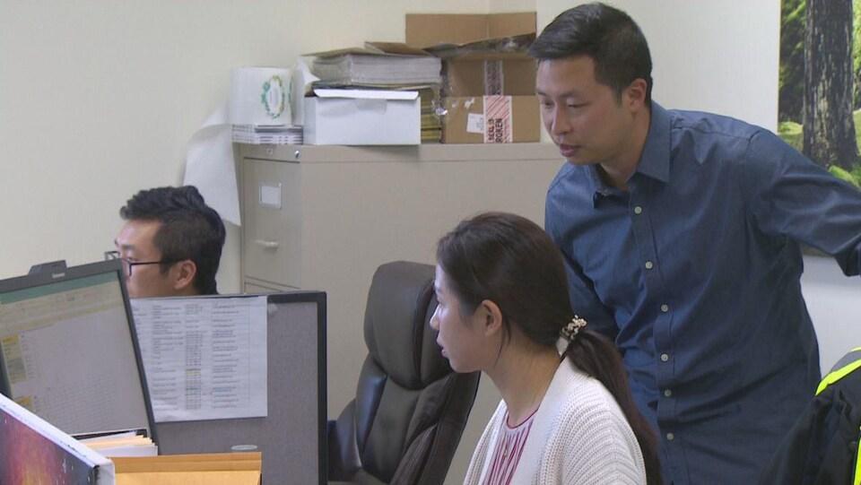 Yang Xue parle à deux des ses employés postés à leur bureau.