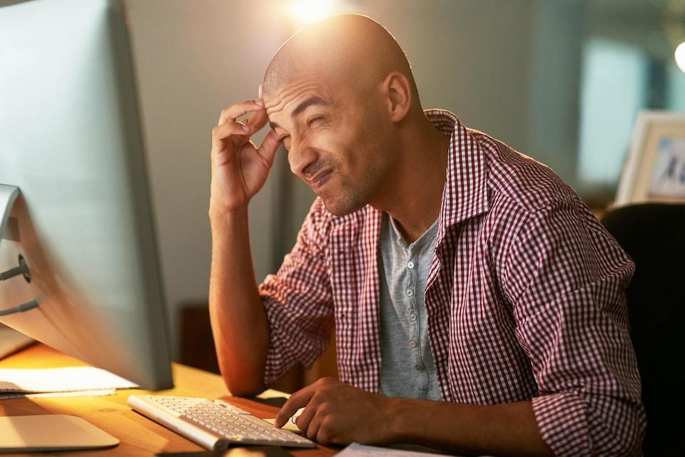 Homme confus devant un ordinateur.