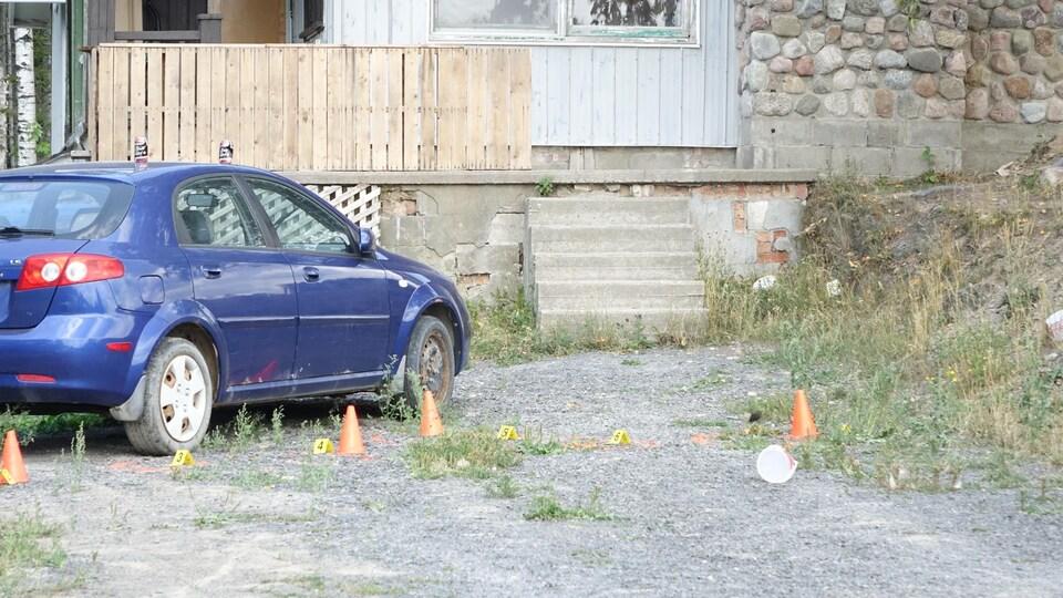 Un véhicule bleu est stationné devant une maison. Des cônes sont installés tout près.