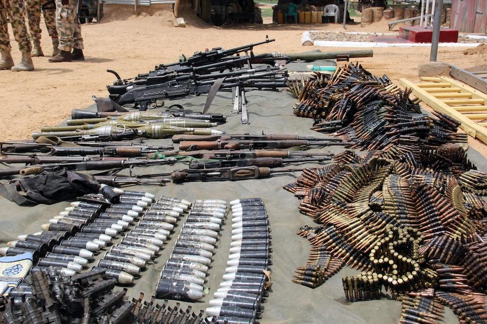 Des munitions, des mitrailleuses et des lance-roquettes sur une bâche.