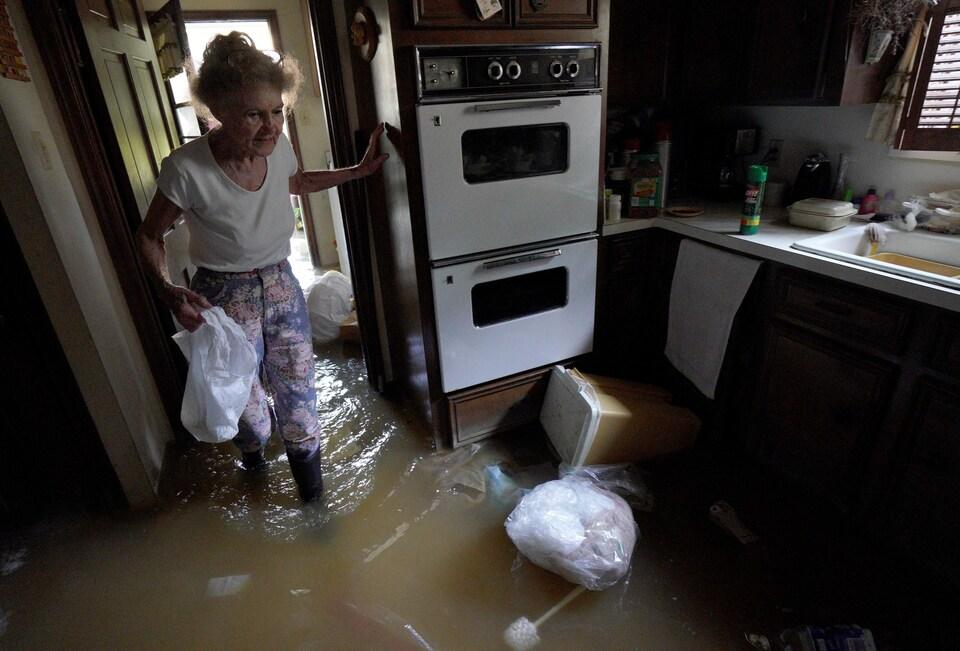Cette femme tente de sauver quelques biens alors qu'elle revient chez elle, à Houston, pour la première fois depuis le passage de l'ouragan Harvey. On la voit se déplacer dans sa cuisine, de l'eau jusqu'aux mollets.