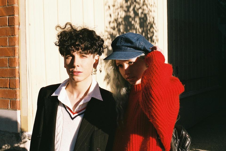 Hubert Lenoir et la jeune écrivaine Noémie D. Leclerc. Ils sont jeunes et beaux. Il a les cheveux noirs et elle,est blonde. Elle porte un pull rouge et une casquette en denim.