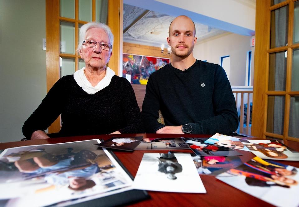 Les deux sont assis devant une table remplie de photos de famille.