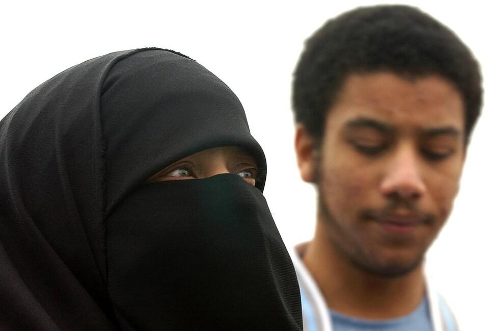 Une femme portant le niqab et un jeune homme en arrière-plan.