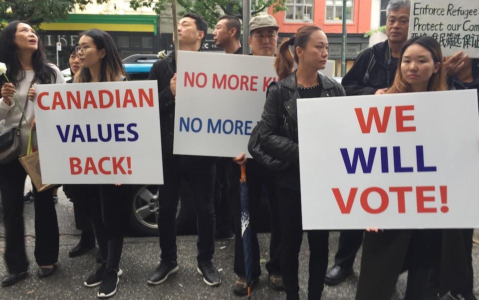 Une dizaine de personnes avec des affiches où on peut lire  Canadian values back, we will vote!