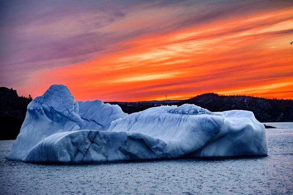Un petit iceberg près de la côte devant un horizon de soleil couchant