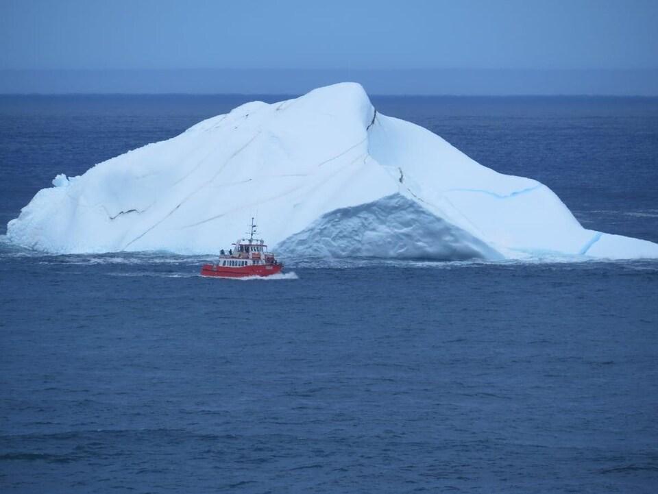 Un bateau d'excursion devant un immense iceberg.