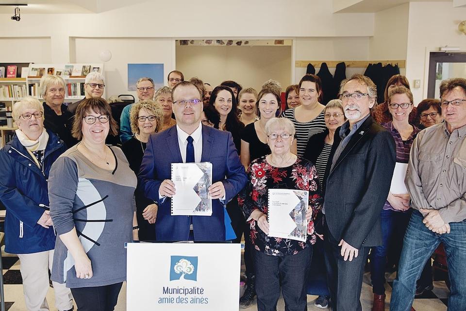 Le maire des Îles-de-la-Madeleine, Jonathan Lapierre, entouré de nombreux contributeurs à l'élaboration de la politique