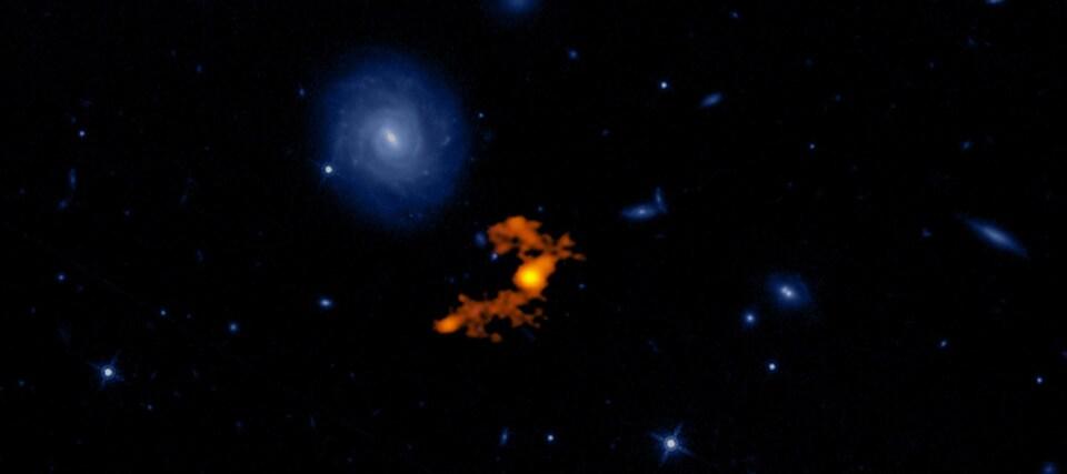 Image composée de la galaxie W2246-0526 et de ses compagnes, avec en toile de fond une image du télescope Hubble de la même région.