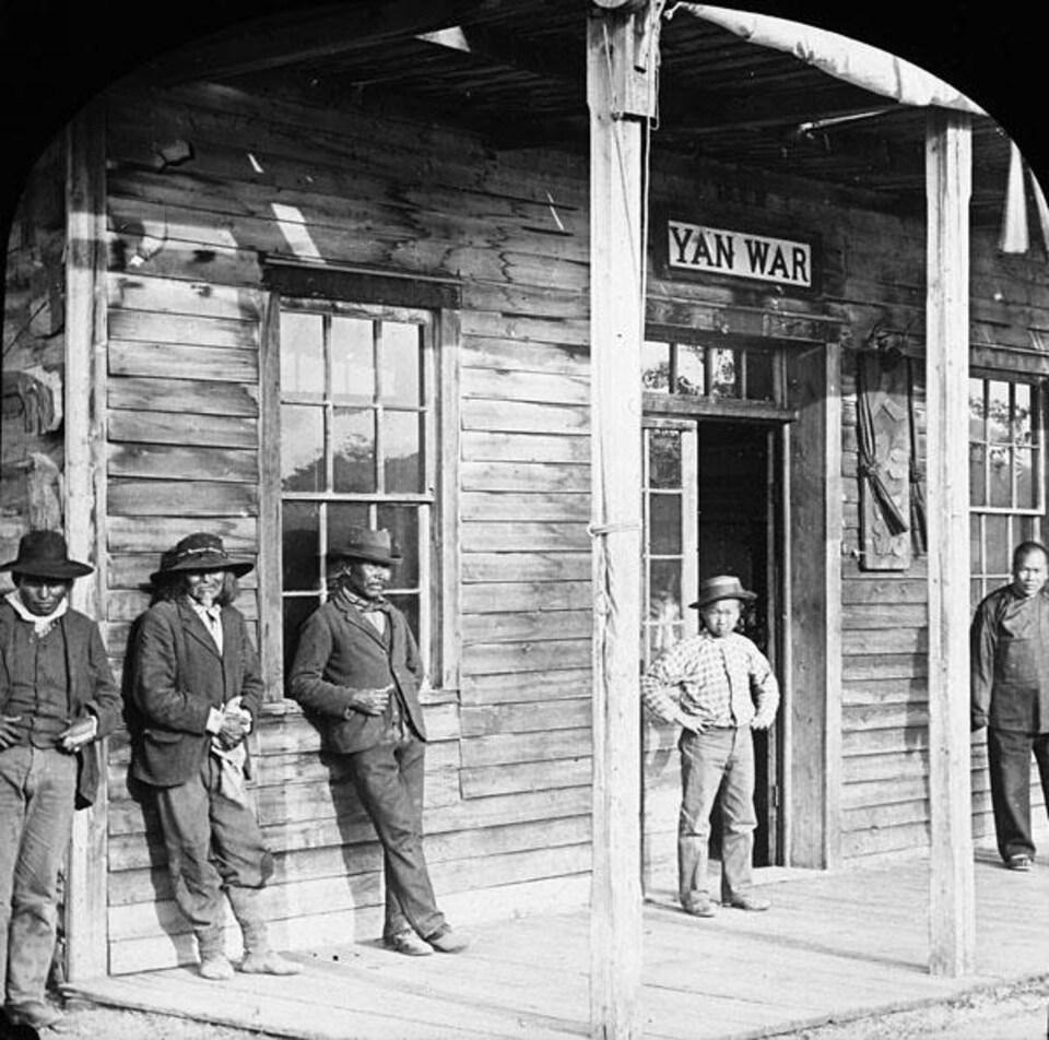 Des hommes se tiennent devant un magasin