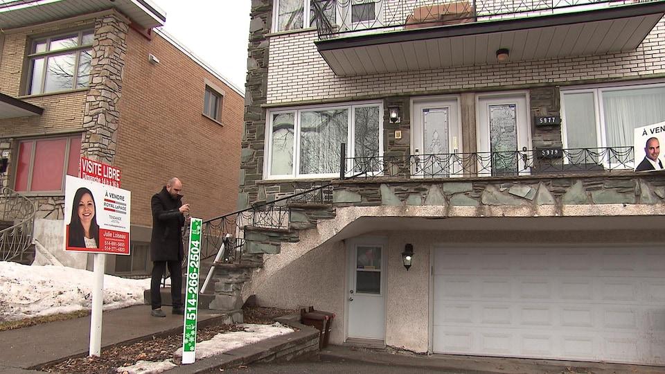 Un agent immobilier pose une pancarte de visite libre devant un triplex.