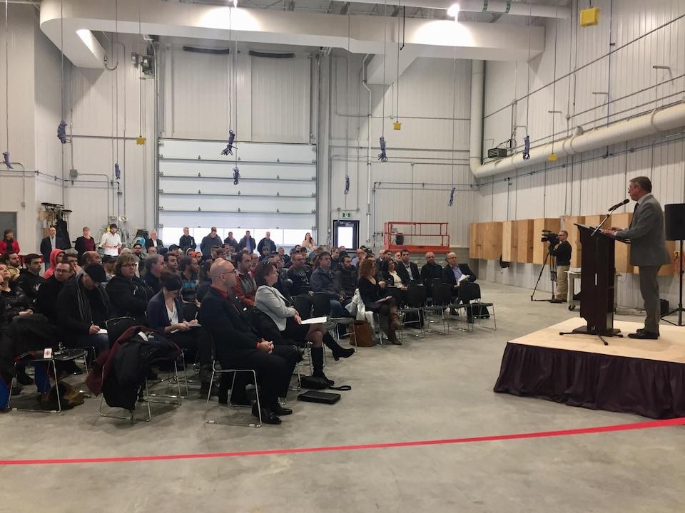 Des dizaines de personnes assises dans un grand garage écoutent un homme qui parle au lutrin lors d'une inauguration.