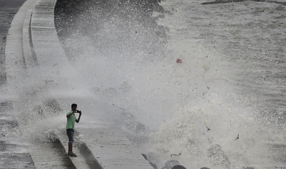 Un homme prend une photo très près de grosses vagues.