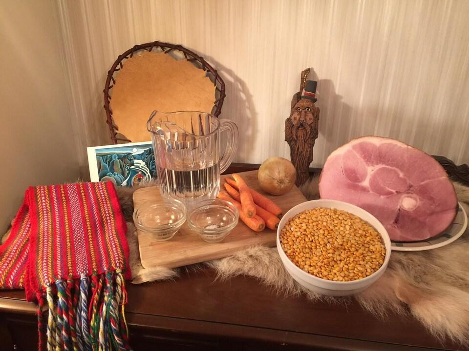 Sur la table, il y a les ingrédients pour la soupe aux pois ainsi qu'une ceinture fléchée et une petite sculpture sur bois.