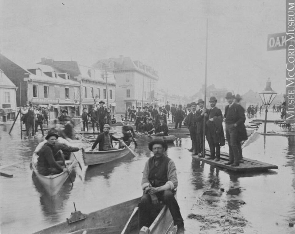 Des hommes dans une embarcation en 1886 lors de l'inondation à Montréal.
