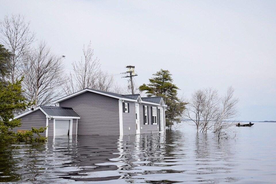 Un canot à moteur passe près d'une maison complètement inondée