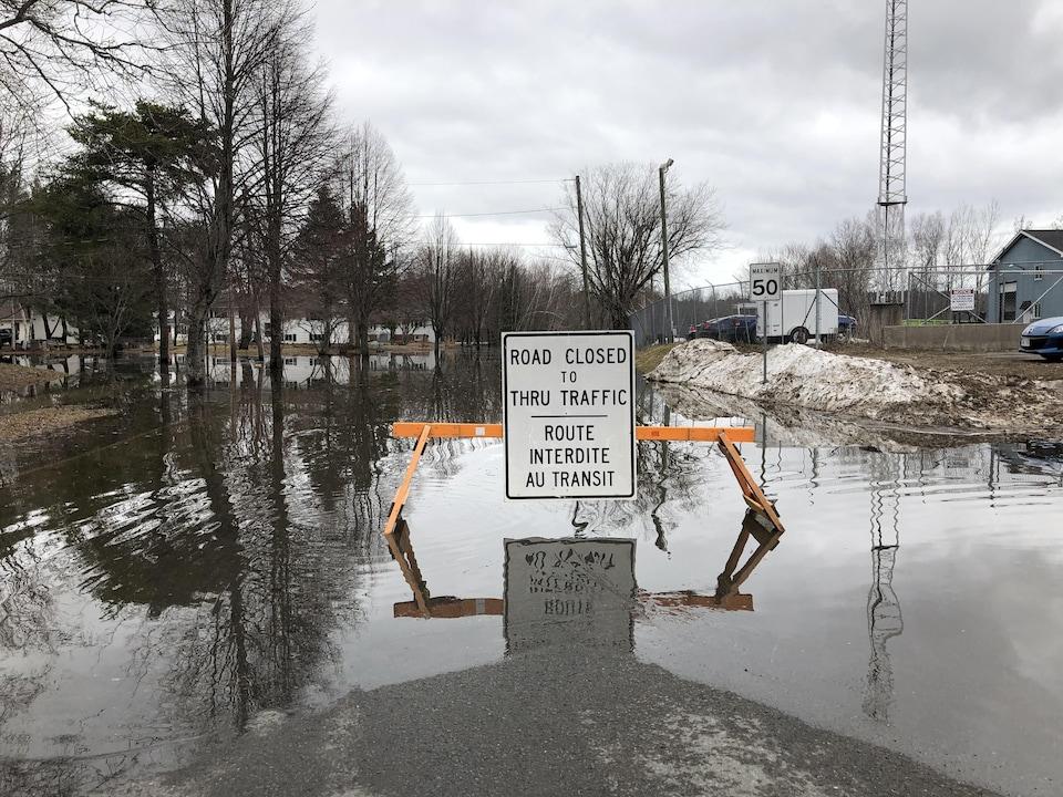 Une pancarte sur une route de campagne inondée indique que la circulation y est interdite.