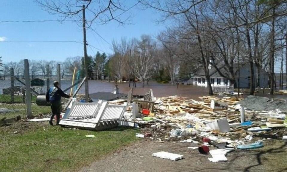 Des débris de bois éparpillés sur le sol avec en arrière-plan une grande maison complètement inondée.