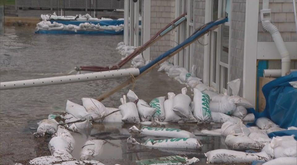 Des sacs de sable empilés le long de la fondation d'une maison inondée