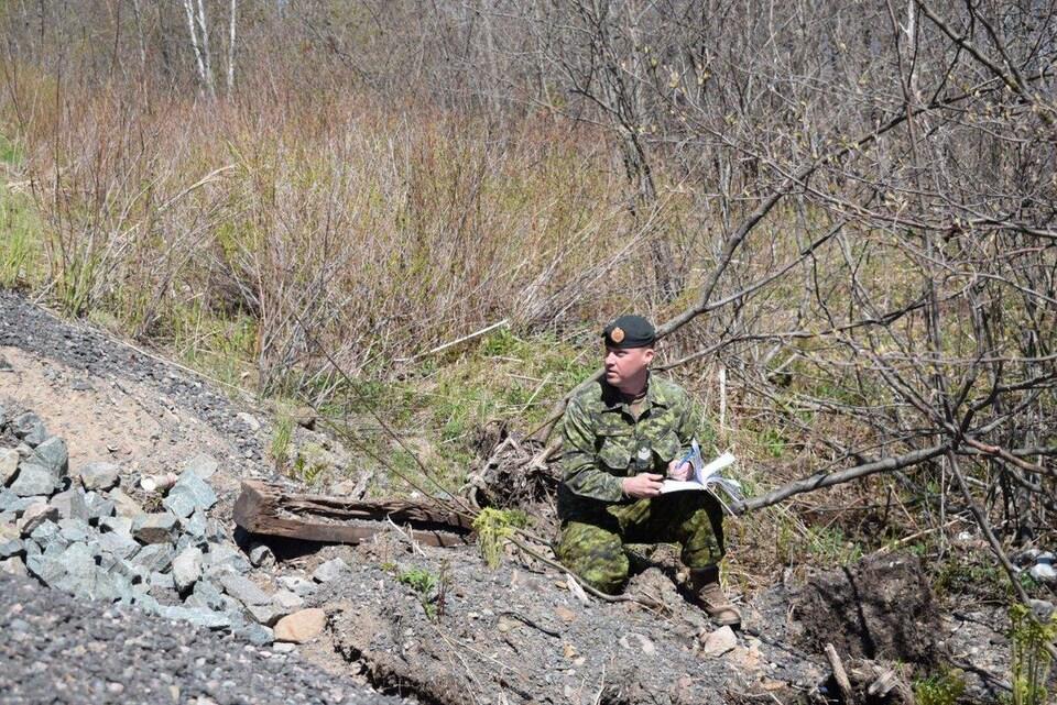 Un soldat qui fait l'inspection d'une route au Nouveau-Brunswick.