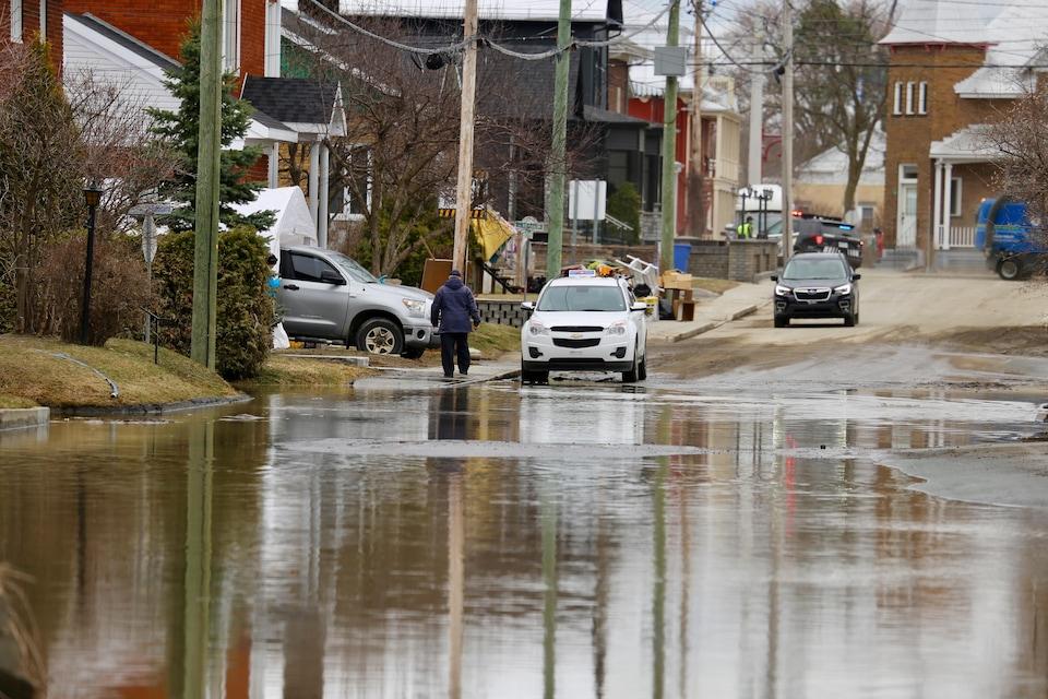 Un homme marche sur le trottoir longeant une rue inondée de Sainte-Marie.