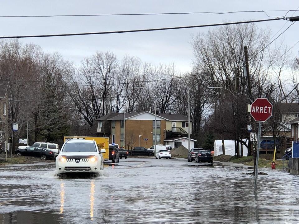 Une voiture tente de traverser une rue inondée.