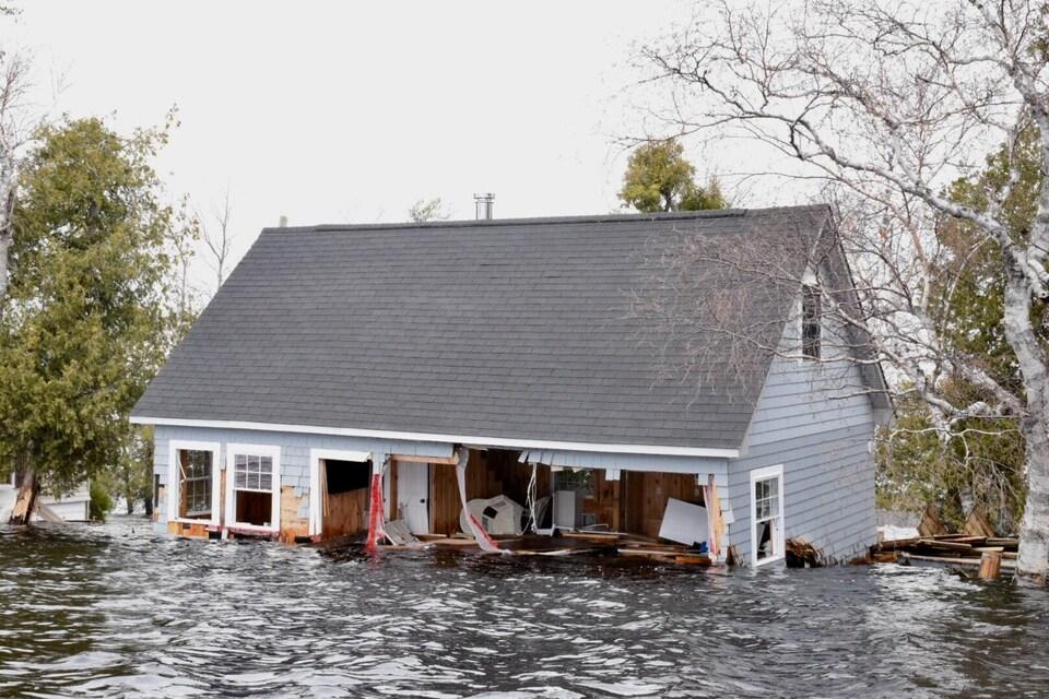 Une partie d'un mur d'une maison inondée est arraché à Princess Park, dans la région de Grand Lake au Nouveau-Brunswick, le 28 avril 2019.